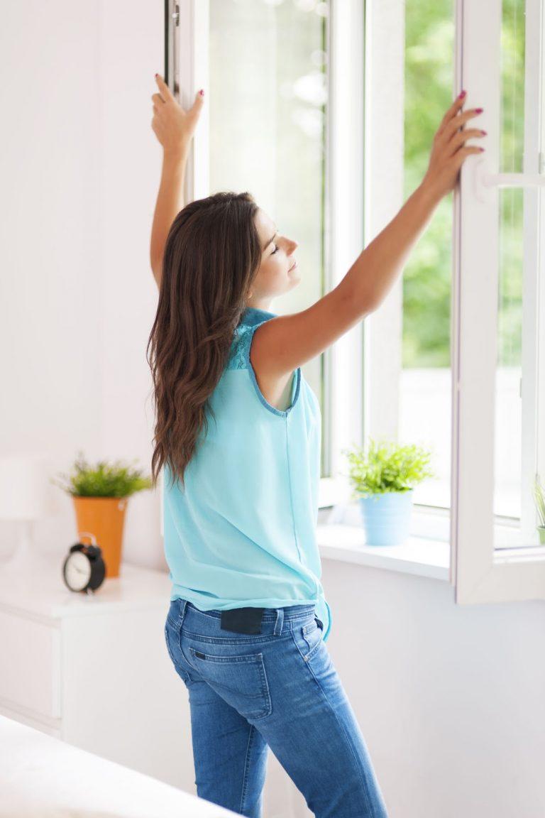 Woman Opening Windows On Beautiful Day